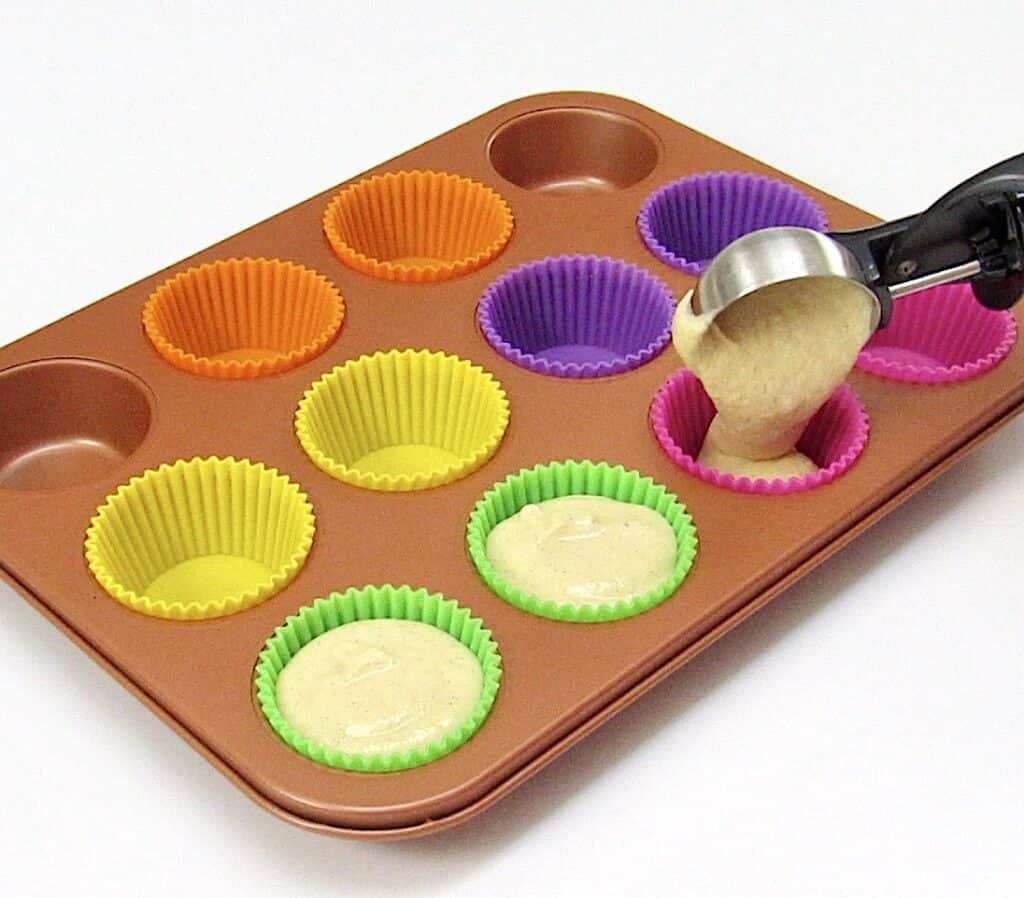 cupcake batter being pour into colorful silicone liners in muffin pan