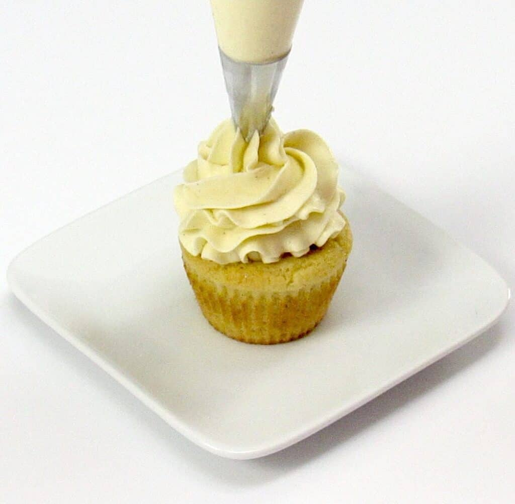 vanilla frosting being piped onto vanilla cupcake