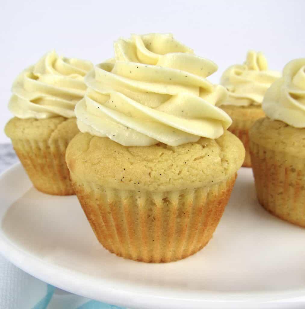 closeup of vanilla cupcakes on white cake stand
