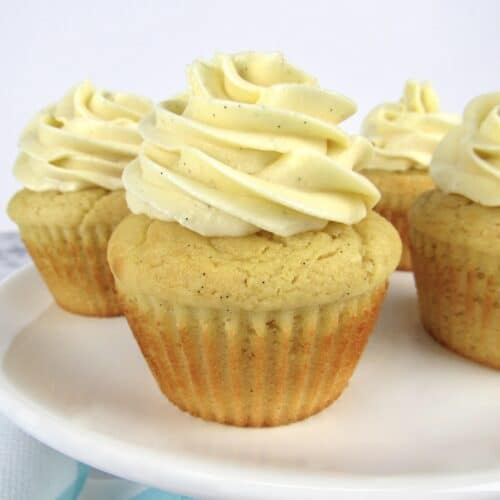 closeup of vanilla cupcakes on white cake stand