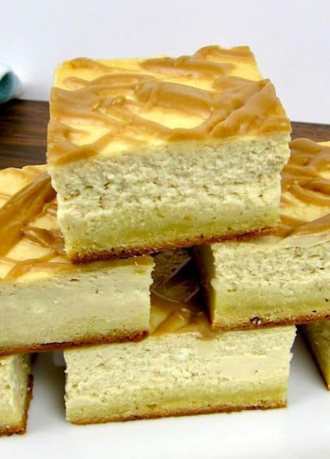 stack of Salted Caramel Cheesecake Bars on white platter