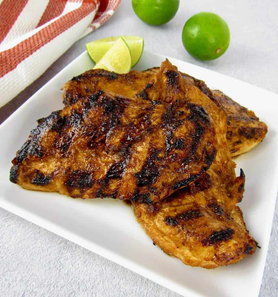 closeup of grilled chipotle lime chicken on plate with lime in background