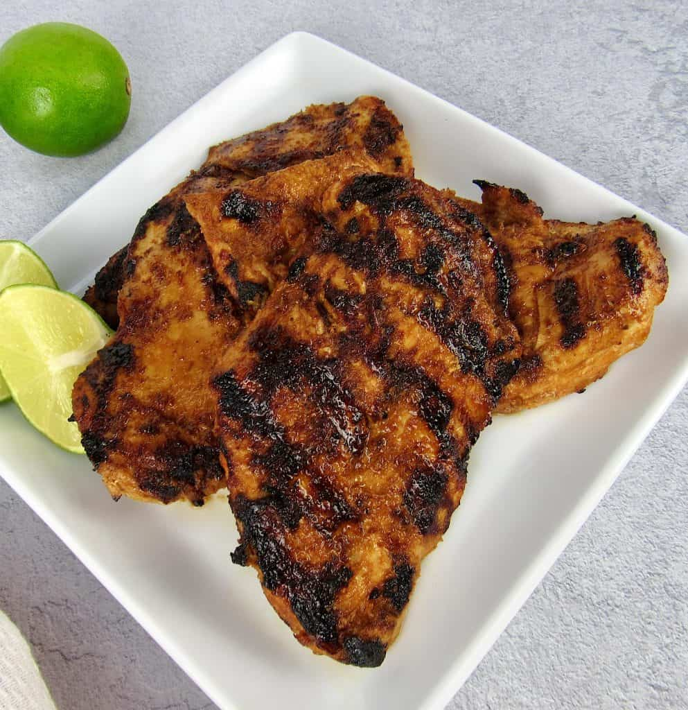 closeup of grilled chipotle lime chicken with cut limes on the plate