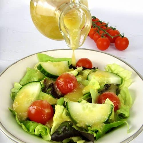 salad with apricot dressing being poured on top