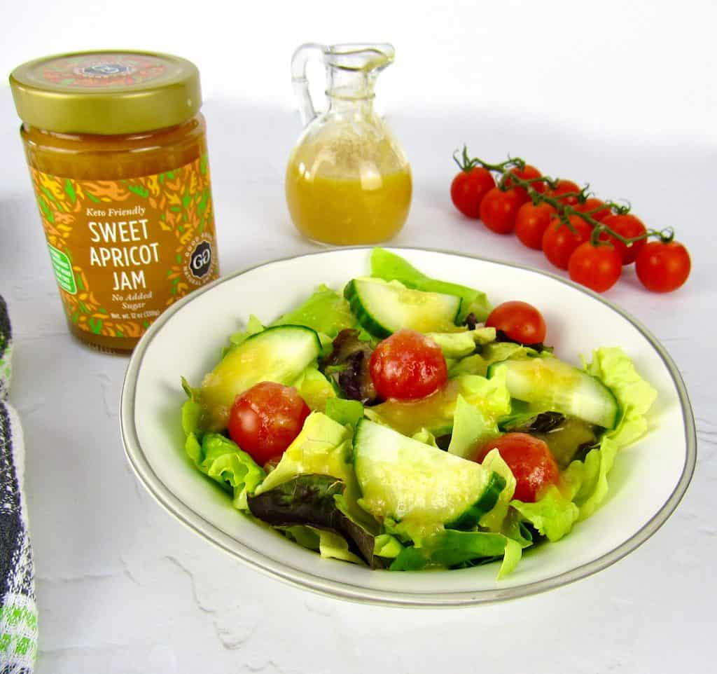 salad with apricot dressing on top and jar of jam in background