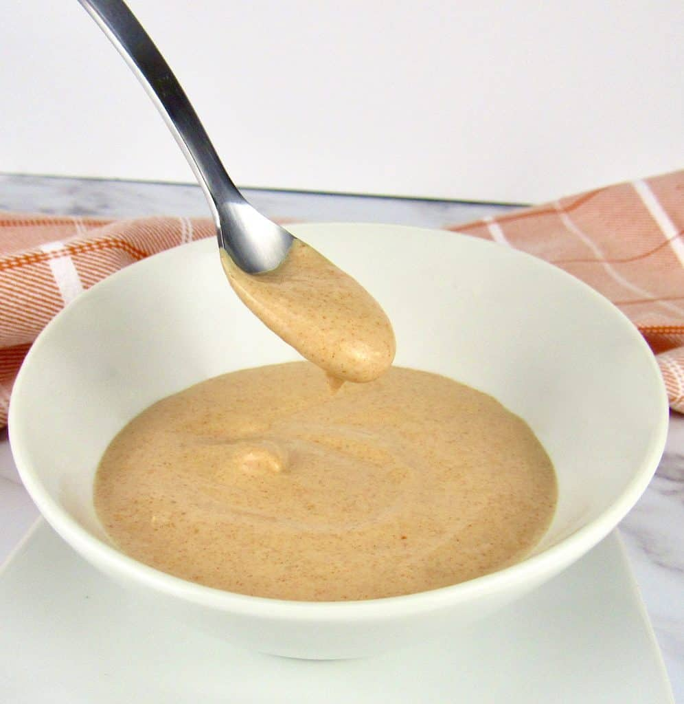 bowl of zesty dipping sauce with spoon holding up some