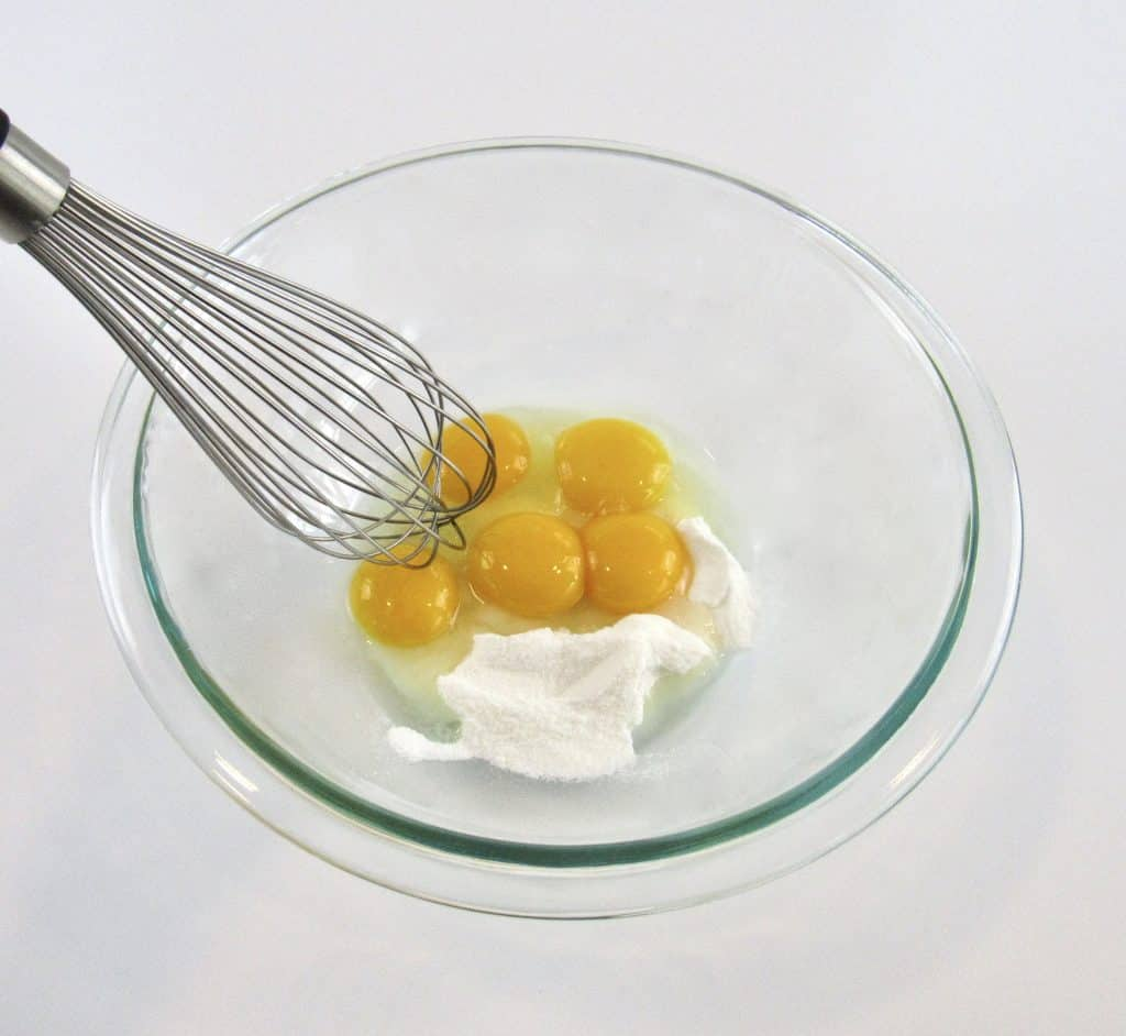 eggs and sugar in glass bowl with whisk