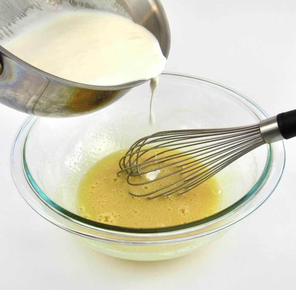 pan pouring hot cream into creme Brûlée mixture with whisk