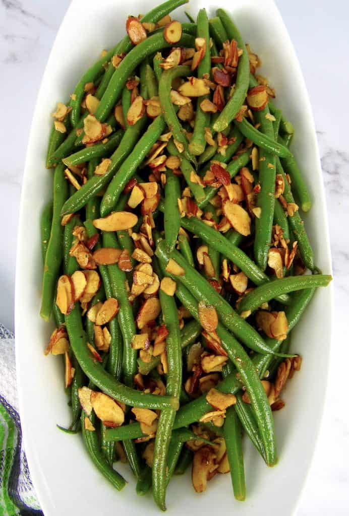 green beans with almonds in white bowl overhead