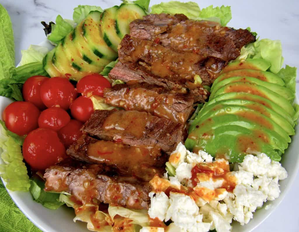 closeup of grilled steak salad with dressing on top
