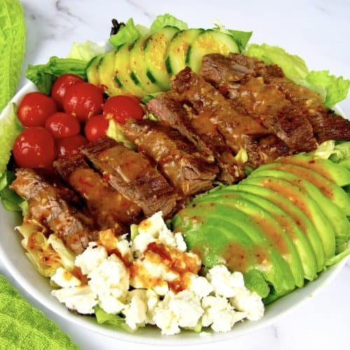 overhead view of grilled steak salad with dressing on top