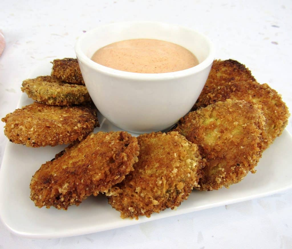 fried pickles on plate with dipping sauce in bowl