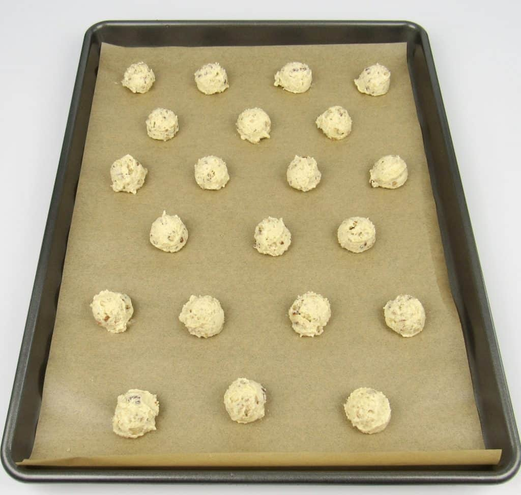 unbaked snowball cookies on cookie sheet