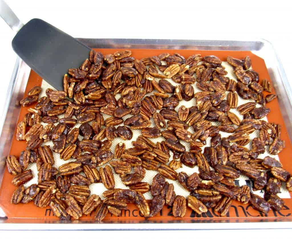 candied pecans spread on baking sheet with spatula