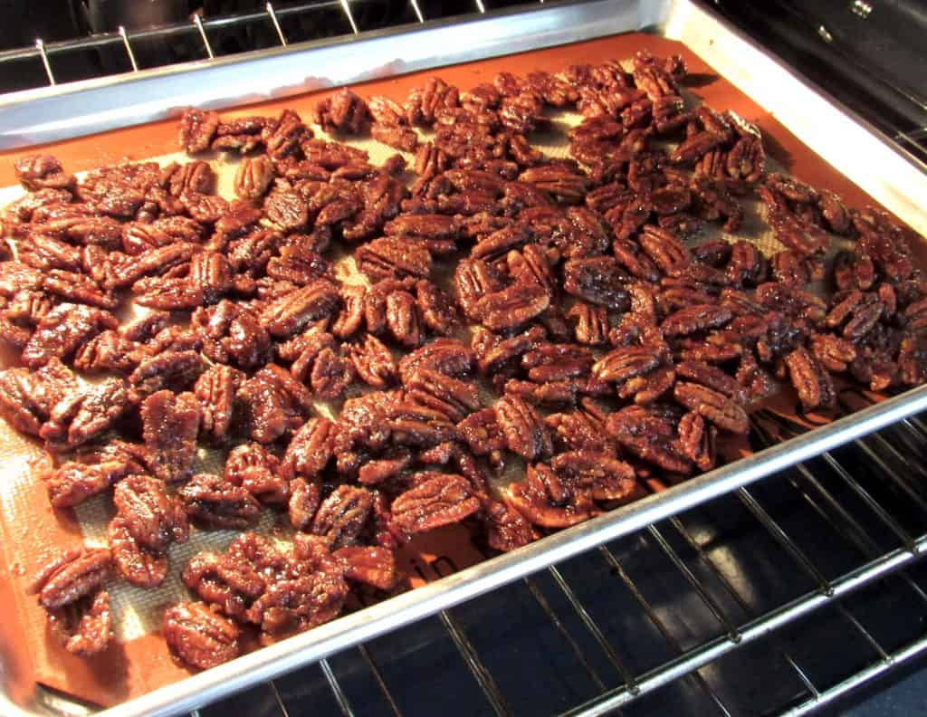 candied pecans baking on sheet pan in oven