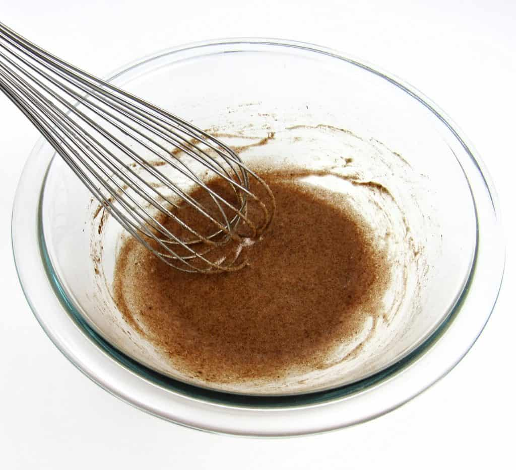 egg white with brown sugar in bowl with whisk