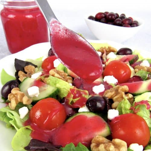 cranberry dressing in spoon held over salad