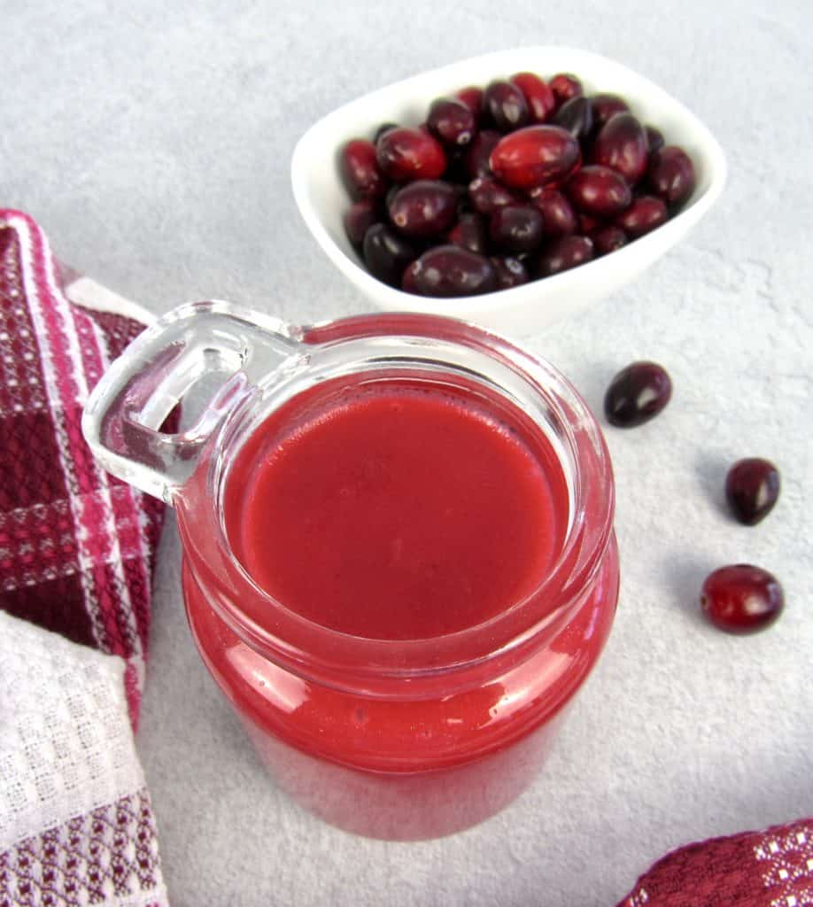 cranberry dressing in glass jar with cranberries in background