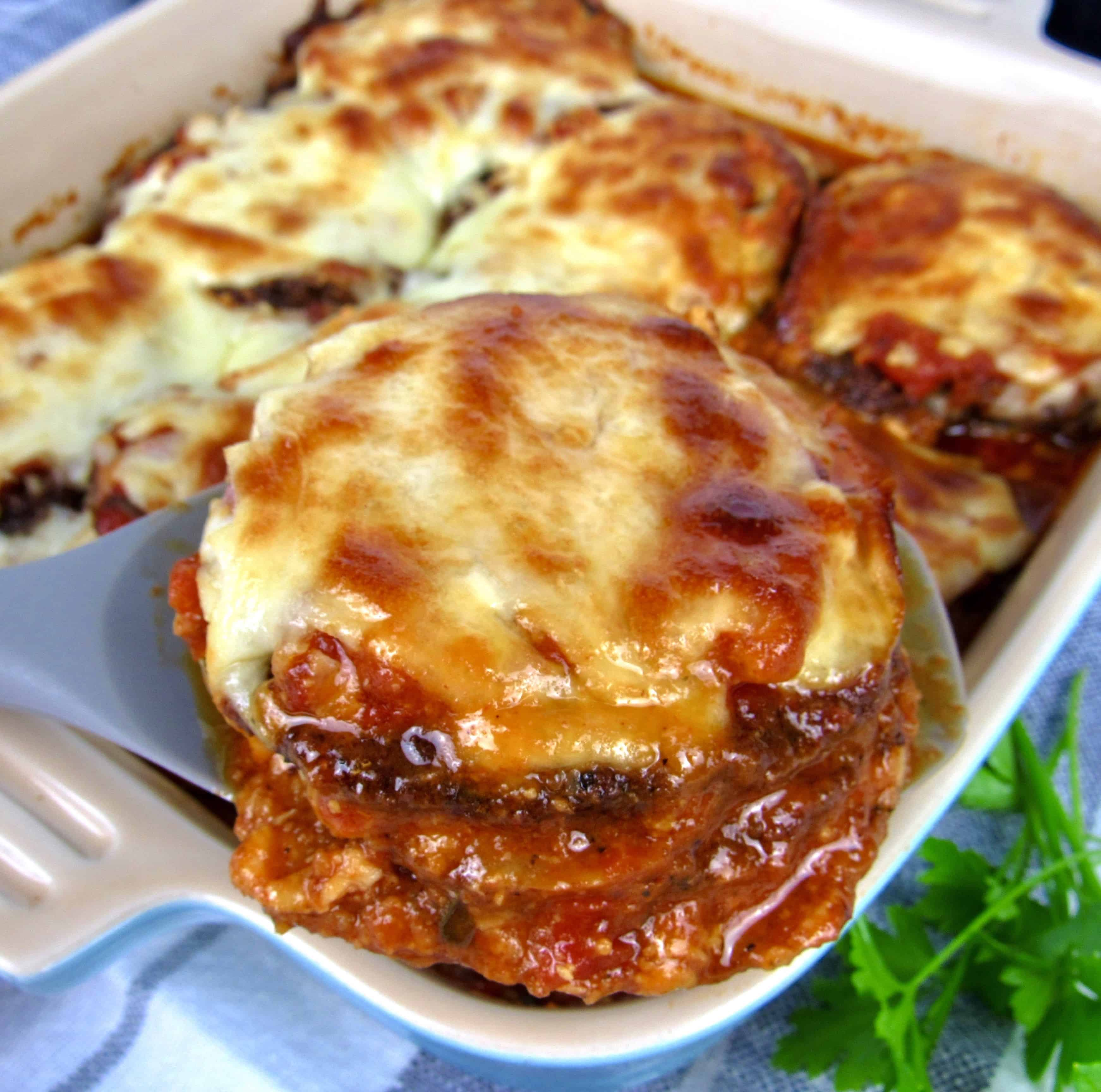 eggplant parmesan being spooned out of a casserole