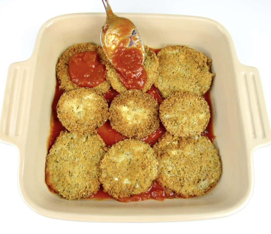 fried eggplant in casserole dish with marinara spooned on top