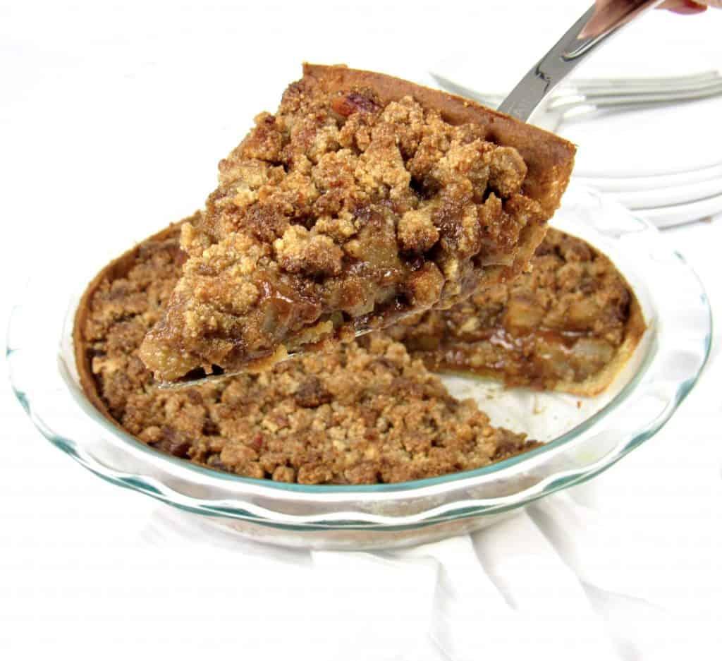 slice of dutch apple pie being held up over pie