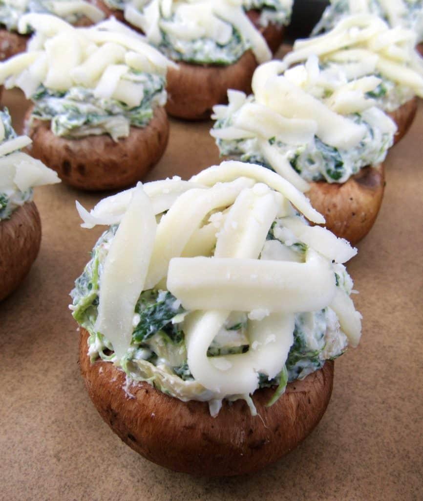 closeup of unbaked Spinach Artichoke Stuffed Mushrooms on baking sheet