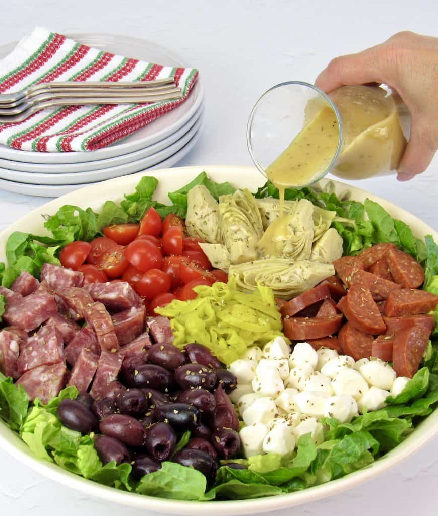 antipasto salad in white bowl with dressing being poured on top