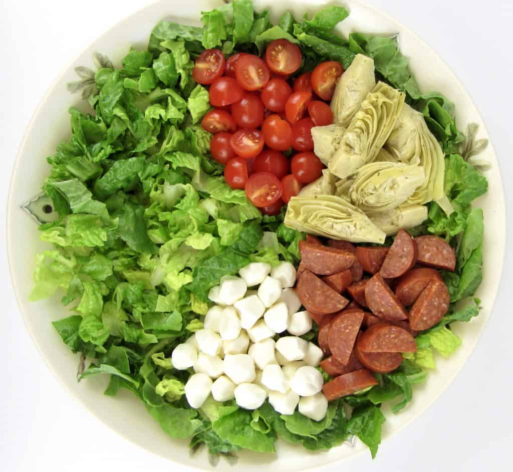 salad with tomatoes, artichoke hearts, pepperoni and mozzarella cheese
