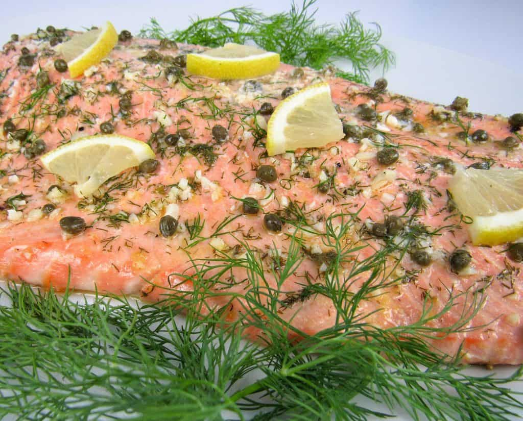 side view of baked salmon with lemon on top and dill on side