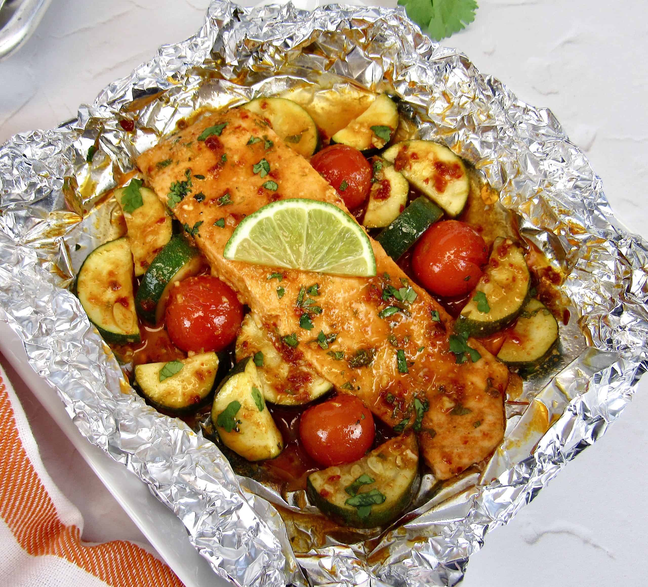 overhead closeup of salmon and veggies in foil baked