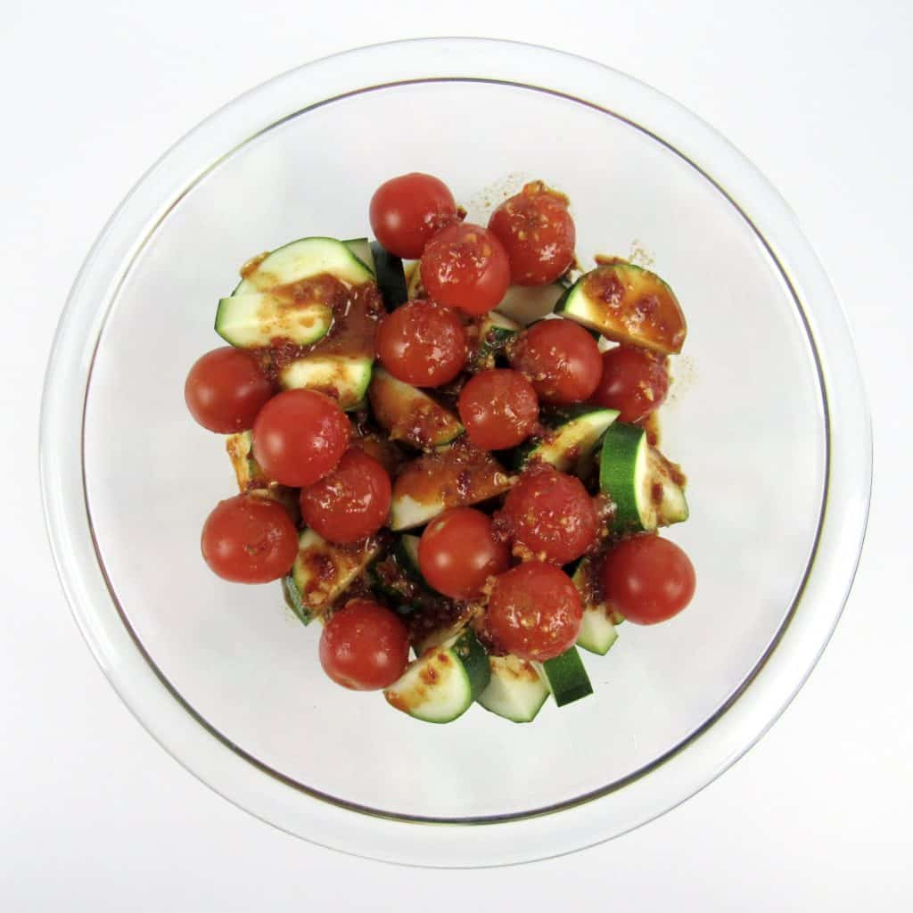 zucchini and tomatoes in glass bowl with marinade