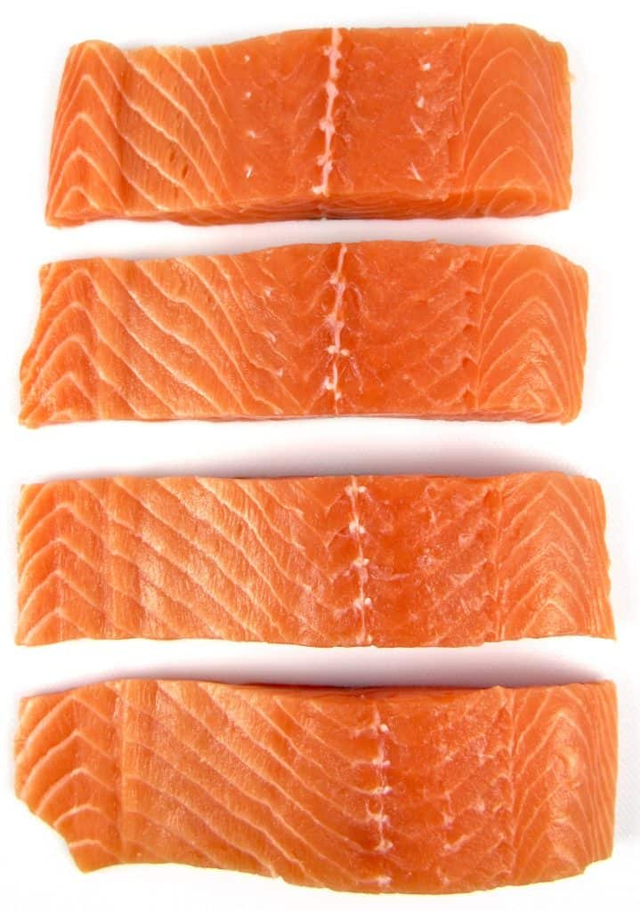 4 pieces of salmon on white cutting board