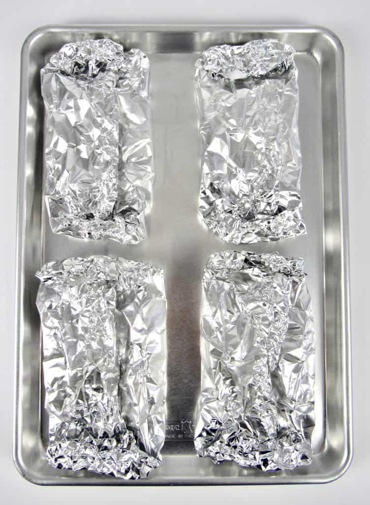 sealed foil packets on baking sheet