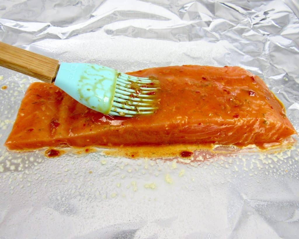 marinade being brushed on salmon on foil