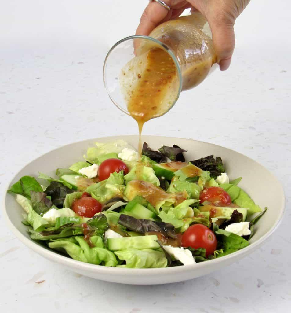 Vinaigrette being poured over salad