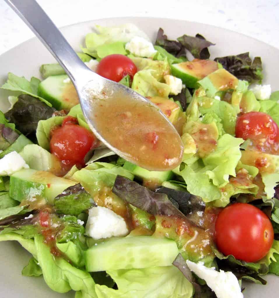 Vinaigrette being spooned over salad