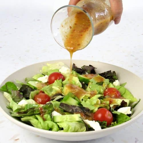 Vinaigrette being poured over salad