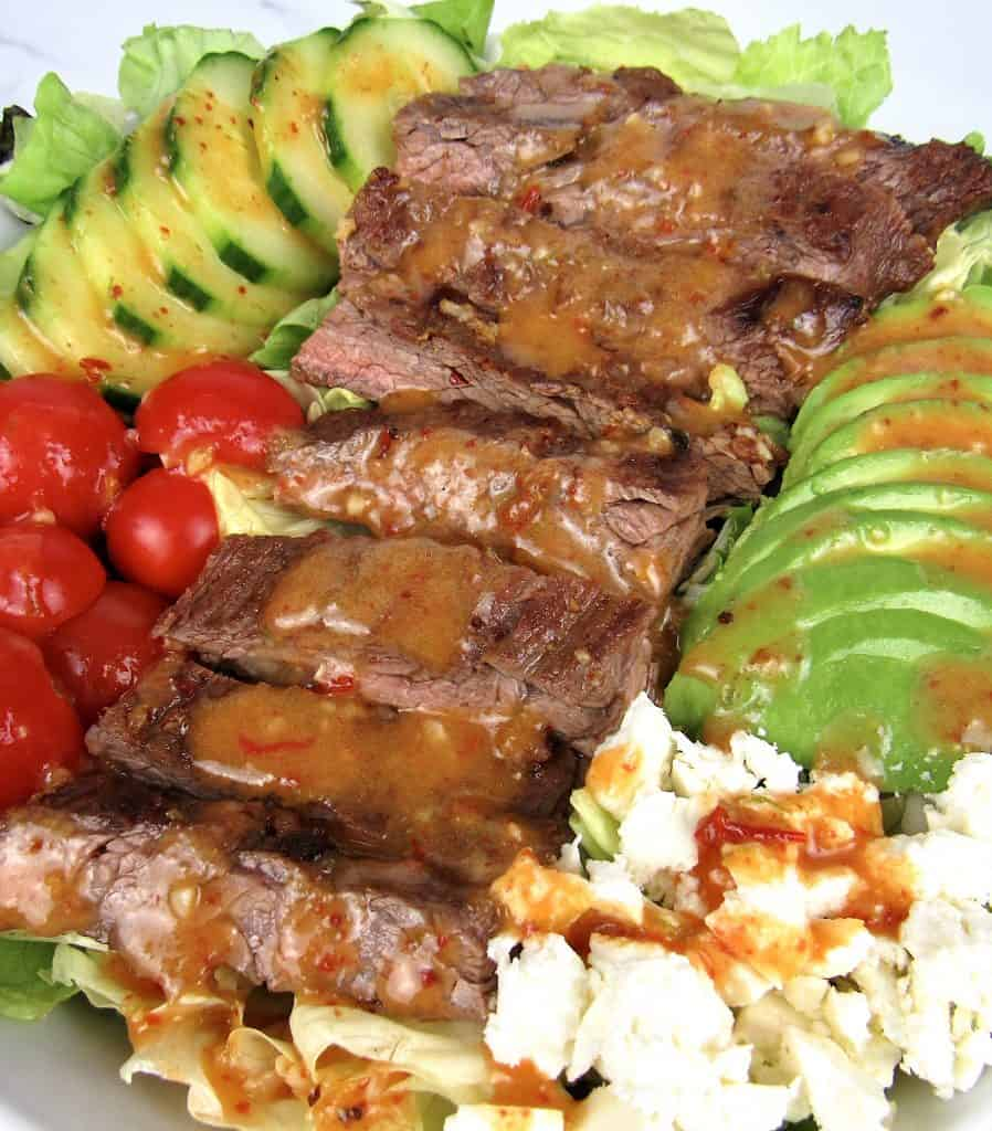 closeup overhead view of grilled steak salad with dressing on top