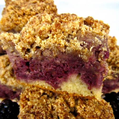 closeup of slices of blackberry coffee cake stacked on plate