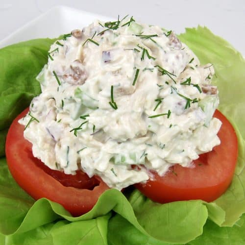 scoop of chicken salad on tomatoes and lettuce