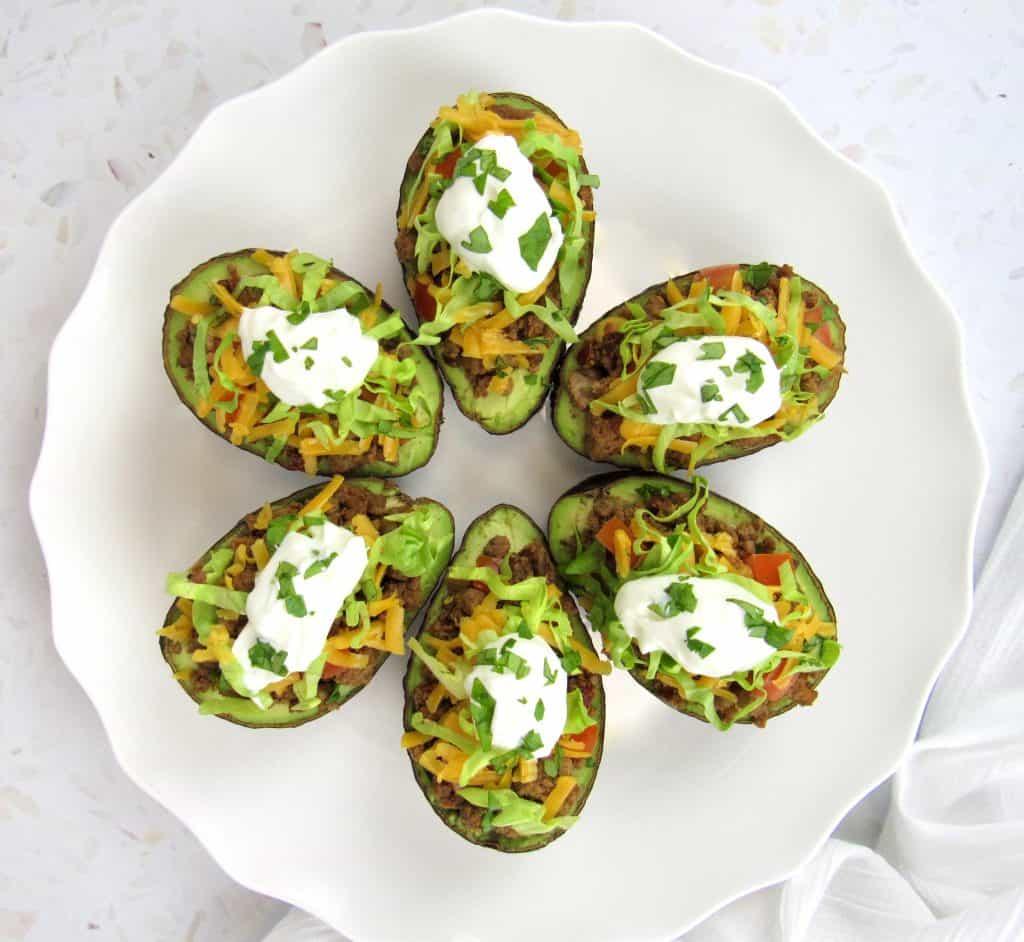 6 taco stuffed avocados on white plate