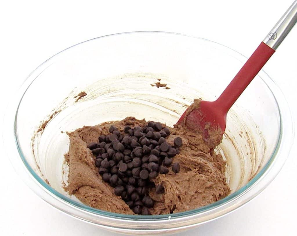 chocolate muffins batter in bowl with chocolate chips on top