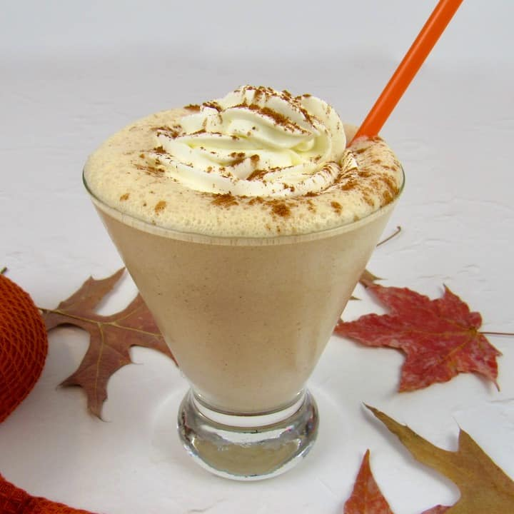 Keto Pumpkin Cheesecake Smoothie with whip cream and red straw