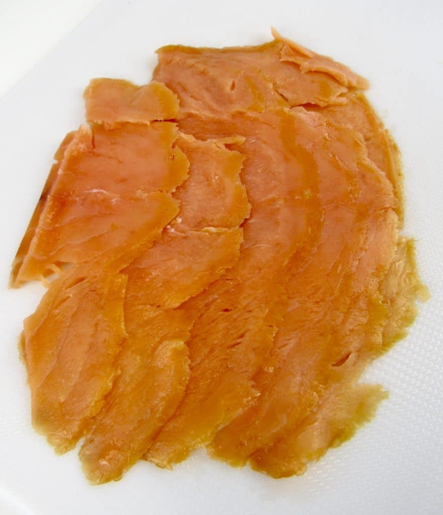 smoked salmon slices on white cutting board