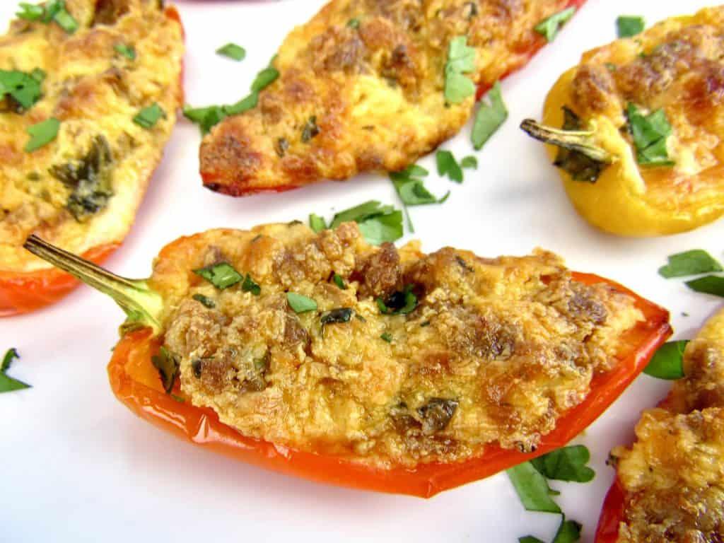 closeup of chorizo and cheese stuffed mini peppers on white plate