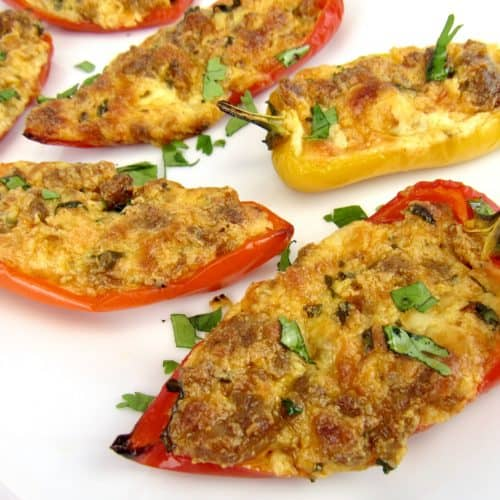 closeup of chorizo and cheese stuffed mini peppers on white plate