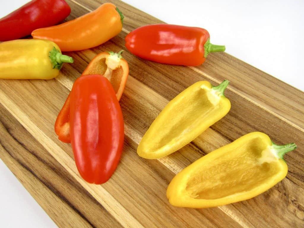 mini red peppers on cutting board cut in half