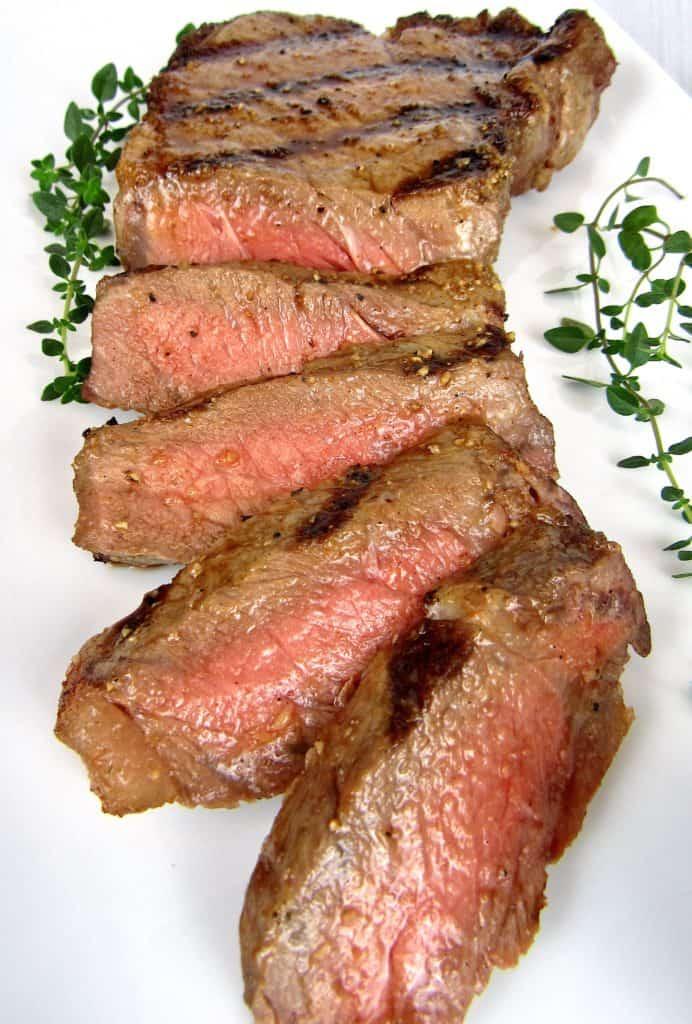 NY strip steak sliced on white platter