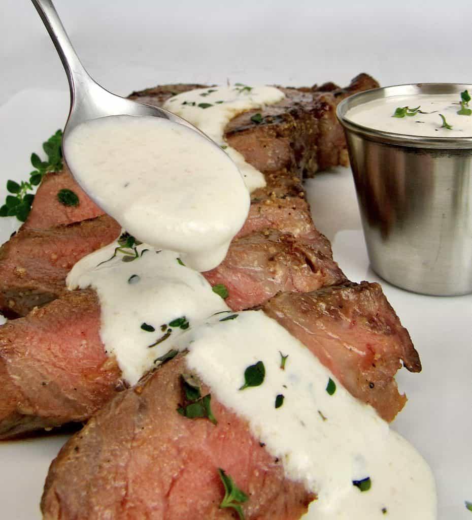 Creamy Horseradish Sauce being spooned over steak slices