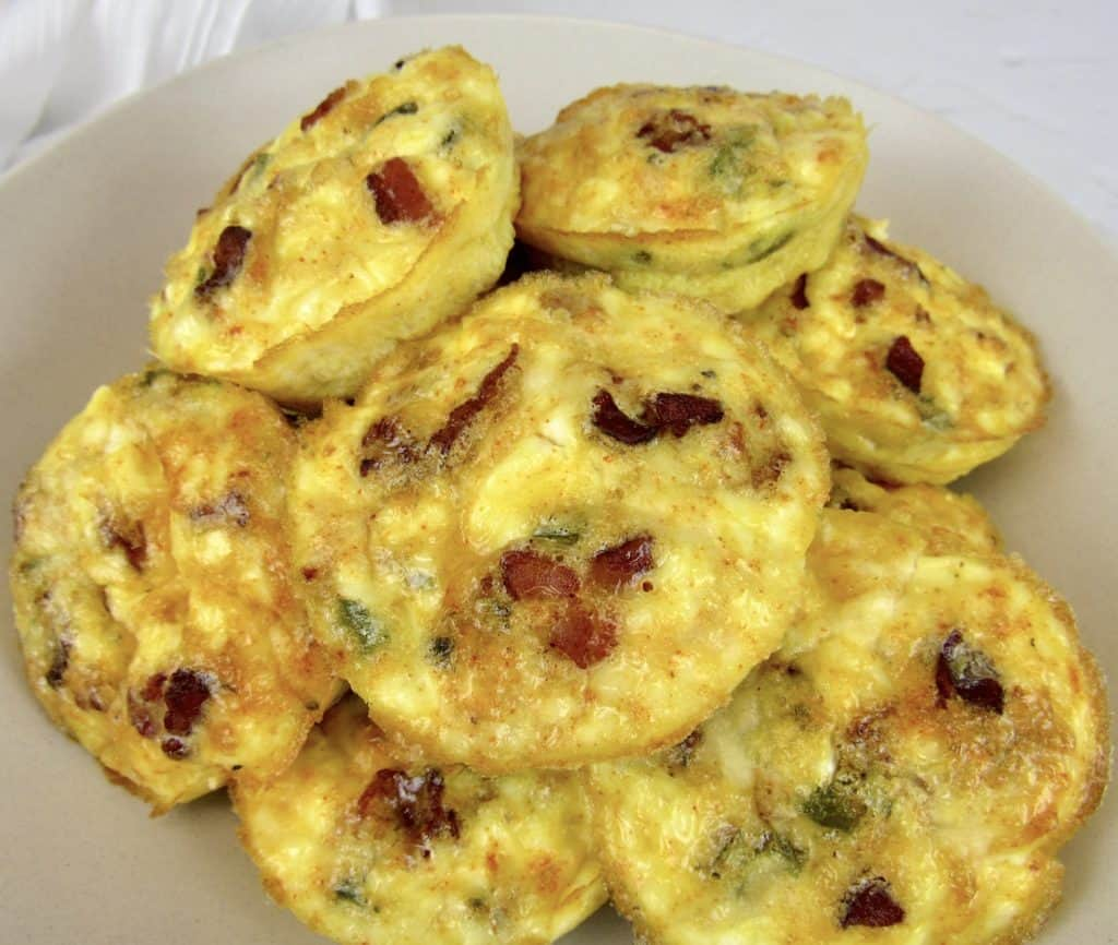 overhead view of Jalapeño Popper Egg Cups piled up in bowl with jalapenos in background